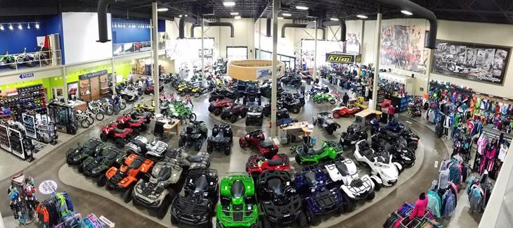 An aerial view of the showroom floor full of brightly colored ATVs, bikes, and clothing.