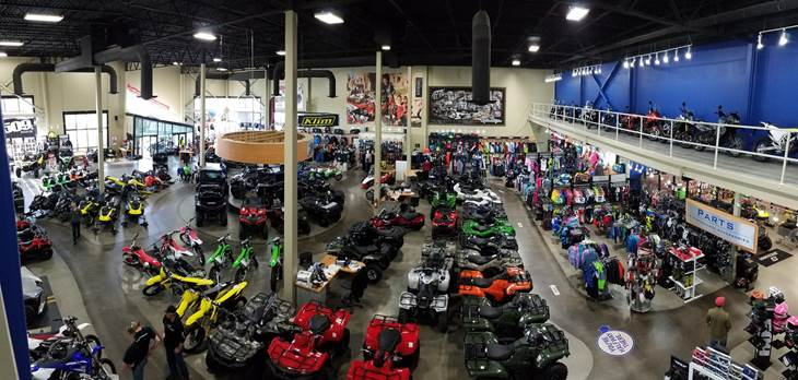 An aerial view of the showroom floor full of brightly colored ATVs and dirt bikes.